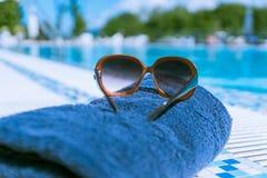 Una imagen de los vidrios y de la toalla de Sun, cerca de la piscina Imagen de archivo libre de regalías