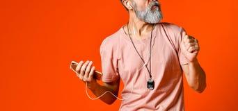 Una imagen de un hombre principal calvo mayor que escucha la música con los auriculares imagen de archivo libre de regalías