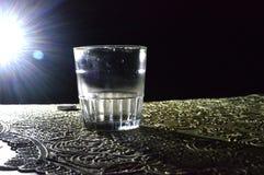 Una imagen de un vidrio en la oscuridad con una poca luz imagen de archivo