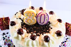 Una imagen del concepto de una torta de cumpleaños con la vela - 80 Foto de archivo libre de regalías