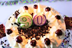 Una imagen del concepto de una torta de cumpleaños con la vela - 90 Imagen de archivo