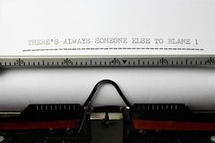 Una imagen del ` de los therealgún otro siempre a la culpa - vivimos nosotros morimos ` escrito en una máquina de escribir - as fotos de archivo libres de regalías