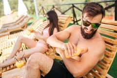 Una imagen del individuo barbudo que se sienta en sunbed y puesto un poco de crema del sunproof en piel de la botella anaranjada  foto de archivo