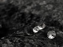 Una imagen del primer de los diamantes dispersados que muestran las facetas de la gema en una roca imagen de archivo