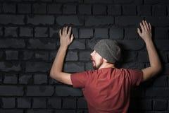 Una imagen divertida de un individuo barbudo, que es buscado por la policía y brilla con una linterna imagenes de archivo