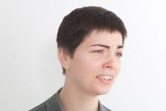 Una imagen fuerte de una mujer muy trastornada y emocional que llora y que grita en el fondo blanco Fotos de archivo