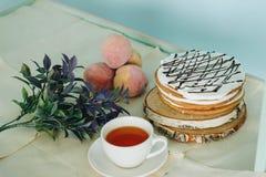 Una imagen inmóvil de la vida de una torta acompañada por un té negro, melocotones e hierbas del af de la taza Imagen de archivo