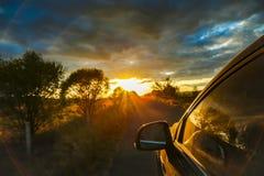 Una impulsión del coche a la puesta del sol Foto de archivo