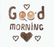 Una inscripción de los granos de café y de las tazas, buena mañana en un fondo blanco Foto de archivo libre de regalías