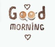 Una inscripción de los granos de café y de las tazas, buena mañana en un fondo blanco Fotografía de archivo