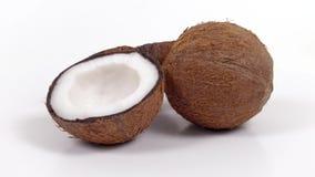 Una intera noce di cocco e due metà con polpa squisita che gira sul bianco hanno isolato il fondo Loopable senza cuciture stock footage