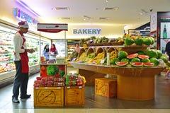 Una isla de la sección de la fruta y una cabina promocional con un promotor en un supermercado en Asia foto de archivo libre de regalías