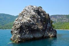 Una isla rocosa en un barranco verde Imágenes de archivo libres de regalías