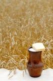 Una jarra de leche y de pan en un campo de trigo Foto de archivo libre de regalías