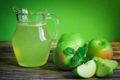 Una jarra de zumo de manzana con las manzanas verdes en una tabla de madera, primer fotos de archivo libres de regalías