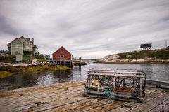 Una jaula vacía en el primero plano, casas del cangrejo en el fondo encontrado en la ensenada de Peggy en Halifax Nova Scotia fotografía de archivo libre de regalías