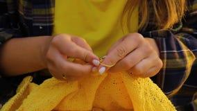 Una joven con el pelo largo y rubio teje un suéter amarillo en el jardín en verano. mujer hace ropa con las manos cerradas almacen de metraje de vídeo