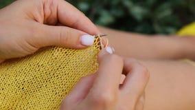 Una joven con el pelo largo y rubio teje un suéter amarillo en el jardín en verano. mujer hace ropa con las manos cerradas metrajes