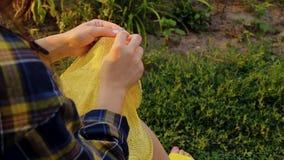 Una joven con el pelo largo y rubio teje un suéter amarillo en el jardín en verano. mujer hace ropa con las manos cerradas almacen de video
