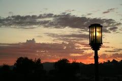 Una lámpara de calle que ilumina en la puesta del sol Imagen de archivo