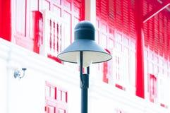 Una lámpara de calle retra en fondo de madera de la puerta roja tradicional Fotografía de archivo libre de regalías