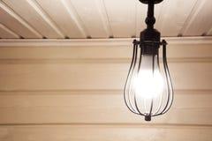 Una lámpara del negro del vintage bajo techo en un cortijo de madera Fotografía de archivo