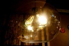 Una lámpara que brilla intensamente misteriosa en un plafond de cristal Fotografía de archivo