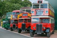 Una línea de autobuses rojos y verdes del vintage del vintage Fotos de archivo libres de regalías