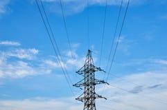 Una línea de cables de tensión contra un cielo azul con las nubes fotografía de archivo