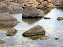 Una laguna sulla spiaggia formata a bassa marea fotografia stock