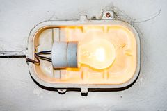 Una lampada bruciante che appende su una vecchia parete rotta fotografie stock