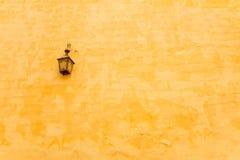 Una lampada d'annata e una parete gialla fotografie stock libere da diritti