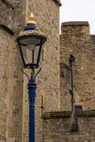 Una lampada sta fuori in oro e nello splendore blu contro il lavoro in pietra smussato delle fortificazioni medievali Immagine Stock