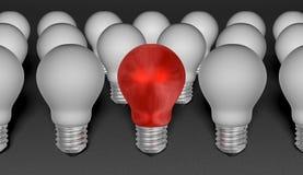 Una lampadina della luce rossa fra grey un su fondo strutturato grigio Fotografia Stock
