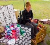 Una lana di filatura dell'alpaga di signora su una ruota di legno Fotografia Stock