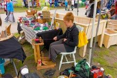 Una lana di filatura dell'alpaga di signora su una ruota di legno Fotografia Stock Libera da Diritti