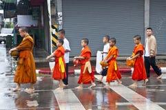Una larga cola de los monjes que reciben el arroz que ofrece de Imagenes de archivo