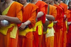 Una larga cola de los monjes que reciben el arroz que ofrece de Fotografía de archivo