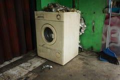 Una lavadora blanca abandonada e inusitada con la puerta principal cerca de la pared verde y de una escoba Depok admitido foto In Foto de archivo