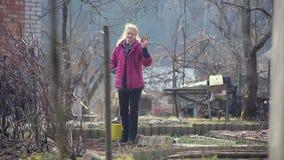 Una lavoratrice agricola lavora la terra con una zappa archivi video