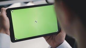 Una lectura del hombre de una tableta con una pantalla verde delante de la cámara 4K almacen de video