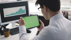 Una lectura del hombre de una tableta con una pantalla verde en la cámara 4K metrajes