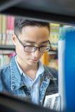 Una lettura asiatica dell'uomo in una biblioteca Immagini Stock