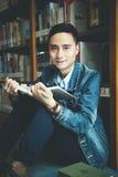 Una lettura asiatica dell'uomo in una biblioteca Fotografia Stock Libera da Diritti