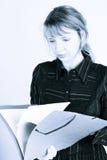 Una lettura della donna attraverso un dispositivo di piegatura (2) immagine stock libera da diritti