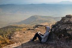 Una lettura di seduta della donna e scrivere osservare fuori la bella vista naturale fotografia stock libera da diritti