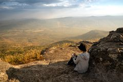 Una lettura di seduta della donna e scrivere osservare fuori la bella vista naturale immagini stock libere da diritti