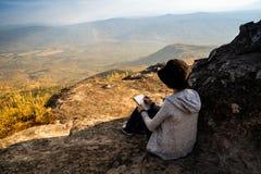Una lettura di seduta della donna e scrivere osservare fuori la bella vista naturale fotografia stock