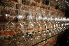 Una linea di vetri di vino lucidati davanti ad un muro di mattoni in una barra di vino fotografie stock