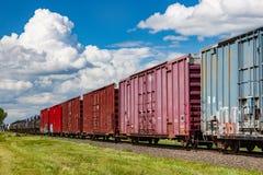 Una linea variopinta di vagoni coperti ferroviari di estate Fotografie Stock Libere da Diritti
